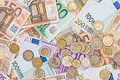 euro coin lying on banknotes close up