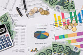 euro bills and coin with busines chart and pen. business concept.