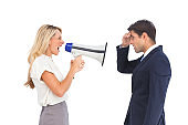 Businesswoman shouting at a businessman with megaphone