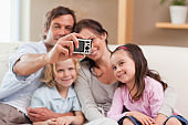 Happy father taking a picture of his family