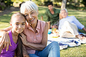 Portrait of grandmother and granddaughter sitting in the park