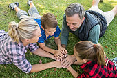 Family lying and putting their hands together in park