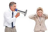 Mature businessman shouting at his coworker with megaphone