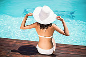 Rear view of woman wearing white bikini and hat sitting near pool