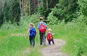 three kids go to school or hiking in nature