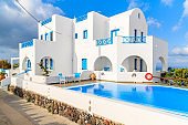 Beautiful holiday apartments with swimming pool in Imerovigli village with typical white Greek architecture, Santorini island, G