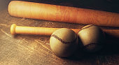 Two baseballs and bats on wooden table
