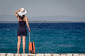 Female tourist with suitcase standing by the sea. Travel and summer vacation concepts.