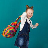 Beautiful smiling little girl with big backpack standing against blue wall