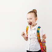 Portrait of a lovely little schoolgirl with big knitted backpack eating delicious lollipop