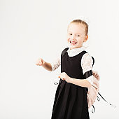 Funny smiling little girl with big backpack jumping and having fun against white background.