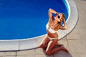 Woman sunbathing in bikini  by the poolside