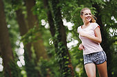 Beautiful jogging woman in nature staying fit and energetic