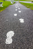 Painted white footprints on asphalt road path as guide