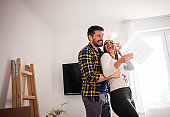 Young couple planning decoration project of new home with blueprint