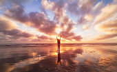 Man On Beach With Arms Outstretched.