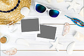 Summer Beach accessories (White sunglasses,starfish,straw hat,shell) and photo frame on white plaster wood table top view,Summer vacation concept,Leave space for adding your photo