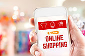 Close up hand holding mobile phone with Online shopping word on screen with blur department store bokeh light background,Digital online marketing concept