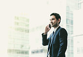 Businessman using mobile phone near office window at office building,communication concept,vintage filter