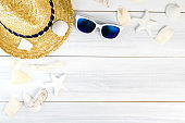 Summer Beach accessories (White sunglasses,starfish,straw hat,shell) on white plaster wood table top view,Summer vacation concept,Leave space for adding text