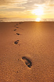 Footprints on the sand at sunset