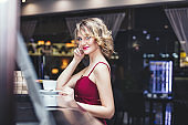 Beautiful woman blonde model in a red jumpsuit elegant with a Cup of coffee in the restaurant