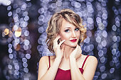 Beautiful woman model with beautiful makeup and red lips the background of glowing bokeh