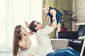 Family mother father and baby are happy together at home smiling
