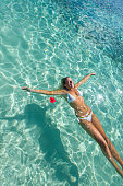 Woman floating on turquoise water on a tropical beach.