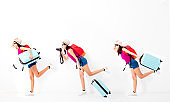 Happy young woman holding suitcase  and running for travel