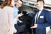 Salesman showing couple the car in showroom