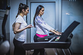 Pregnant woman exercising with a fitness instructor at the gym