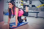 Beautiful young pregnant woman exercising in the gym