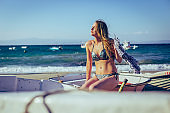 Young happy woman sitting on the boat at the beach and enjoying sunny day