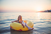 Beautiful woman floating on water and drinking cocktail