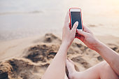 Close-up of woman using phone on the beach