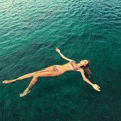 Woman in bikini relaxing lying on the water