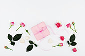 Greeting card from gift box and pink roses. Flat lay.