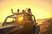Five young people having fun in convertible car at the beach at sunset.