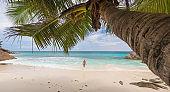 Woman enjoying Anse Patates picture perfect beach on La Digue