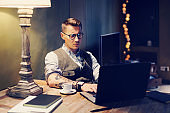 Elegant tattooed man working at home on laptop while sitting at the wooden table.Using modern computer for research new startup ideas.Concept of business people work.Blurred background.