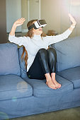 Young beautiful woman using virtual reality headset while working from home