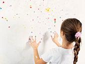 Little girl finger painting her room