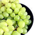 Ripe green grape berries in black round bowl top view