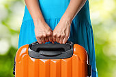 Woman in blue dress holds orange suitcase in hands on natural background