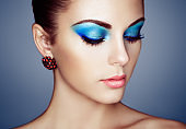 Portrait of young beautiful woman with blue makeup