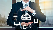 Businessman holding a cloud connected to many objects