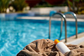 Towel and suntan lotion by the swimming pool