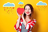 Woman with heart shape box on yellow background
