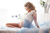 Pretty smiling pregnant girl is wearing blue boudoir dress lying in bed